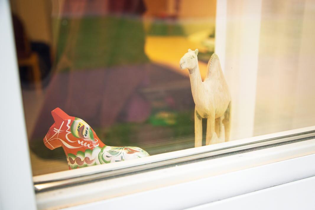 Dalahäst och prydnadskamel i ett fönster